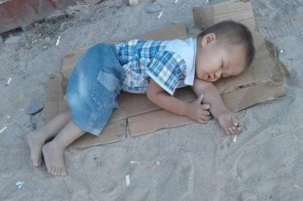 Mãe coloca filho para dormir sobre papelão em mercado de rua e imagem repercute nas redes Facebook / Reprodução/Reprodução