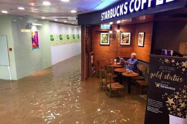Idoso lê jornal e toma café em meio a enchente Kristy Chan / Reprodução/Reprodução