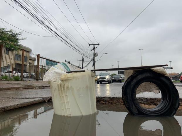 Com madeira, pneu e cesto de máquina de lavar, morador sinaliza buraco em avenida de Porto Alegre Tiago Boff / Agência RBS/Agência RBS