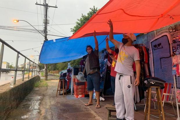 Com camelódromo fechado, comerciantes instalam lonas e se abrigam sob marquises na Restinga Tiago Boff/Agencia RBS