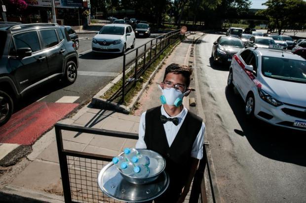 Com gravata borboleta e trajes de garçom, estudante encara calor de 40°C para vender água em sinaleiras de Porto Alegre Marco Favero/Agencia RBS